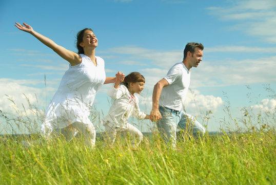 Happy family run on meadow