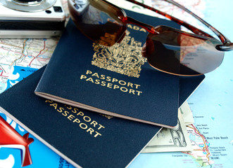 Travel necessities: sunglasses, passports, camera, dollars, map