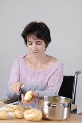 femme handicapé dans chaise roulante préparant le repas