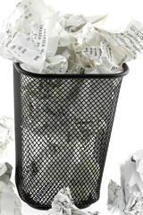 poubelle métallique pleine de tickets de caisse, fond blanc