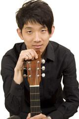 asia boy plays his guitar