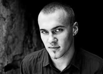 Obraz Młody przystojny mężczyzna z poważną miną w czerni i bieli - fototapety do salonu