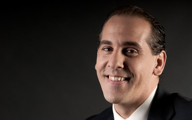 Adult businessman closeup portrait smiling on dark background.