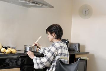 Femme handicapé dans chaise roulante préparant le diner