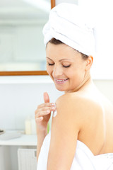 Merry young woman putting cream on her body wering a towel