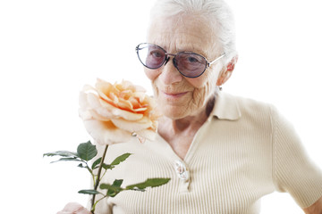 Happy senior woman with rose flower over white background