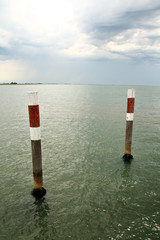 Two wooden signal columns in the middle of sea waters