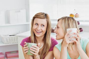 Joyful caucasian friends drinking coffee after baking