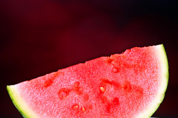 Watermelon slice set against a red background