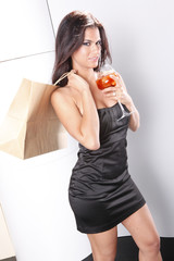 Sriking brunette holds a cocktail glass and shopping bag