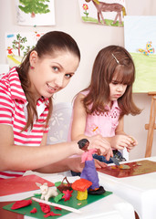 Mother and  daughter playing plasticine.
