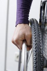close-up d'une main sur uneroue de chaise roulante