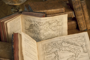 Vintage books and old maps on a wooden table.