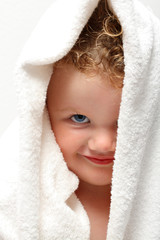 Cute baby girl smiling under a white towel with one eye covered