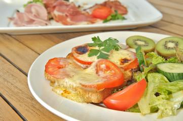 Käsetoast mit Tomaten Kiwi und Salat