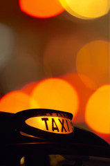 british london black taxi cab sign at night with colorful backgr