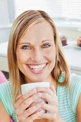 Glowing woman holding a cup of coffee at home