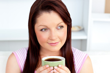 Caucasian woman holding a cup of coffee at home
