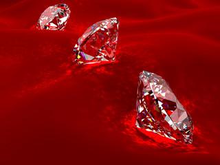 Drei klare Brillianten auf rotem Samt