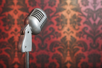 vintage microphone on stand photographed against wallpaper