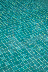 Background of rippled pattern of water in a green swimming pool