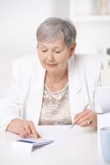 Senior woman using calculator