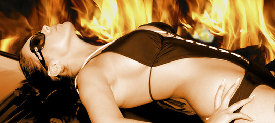 Frau auf Motorhaube vor Feuer