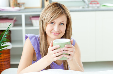 Glowing woman holding a cup of coffee in the kitchen