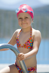 Little child in bathing cap, glasses on the swimming pool stairs