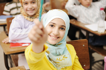 Adorable Muslim girl in classroom with her friends Wall mural