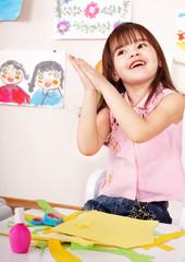 Child glue paper in preschool. Child care.