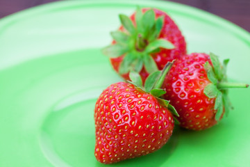 Strawberries and a plate on a bamboo mat