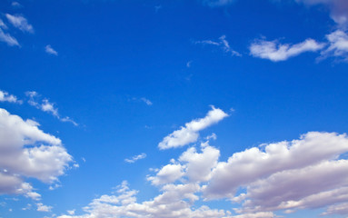 Scattered white clouds with bright blue background