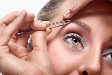 Woman tweezing eyebrow