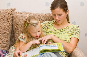 Девочка с мамой читают книгу на диване
