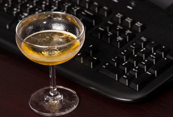 Wine glass and black keyboard on the desk