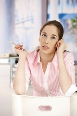 Young  woman in office talking on phone