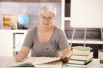 Senior teacher in school searching in a book