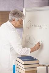 Senior teacher drawing molecular formulas