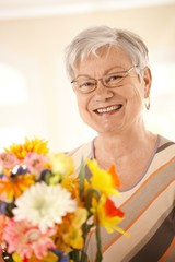 Portrait of happy senior woman with flowers