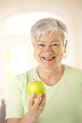 Healthy senior woman holding apple