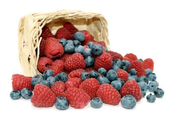 Raspberries, blueberries and wicker basket.