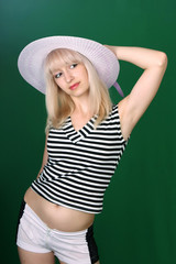 beautiful girl in the hat on a green background