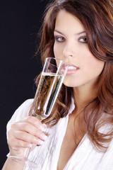 Hübsche Frau hält Sektglas in der Hand, trinkt auf Neujahr