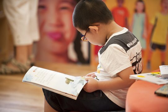 asian boy with glasses read book