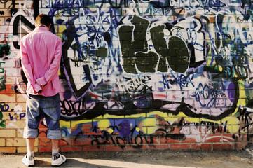 Teenager against graffiti wall.