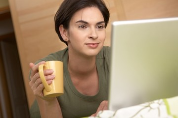 Woman looking at laptop screen smiling at home