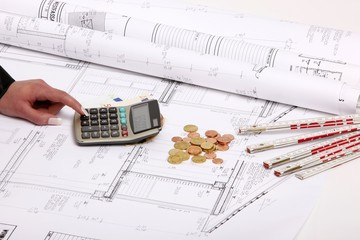 hand with house construction plan, calculator, coins