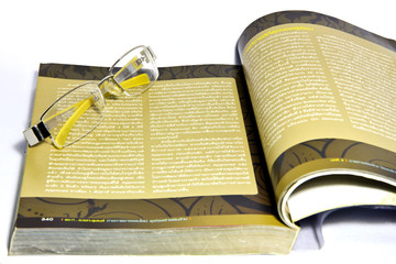 yellow spectacles on a book ,