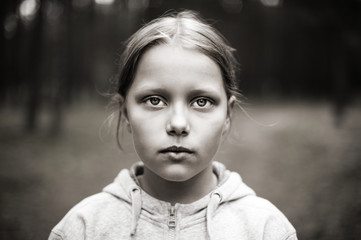 Black and white portrait of tired little girl with sad eyes.